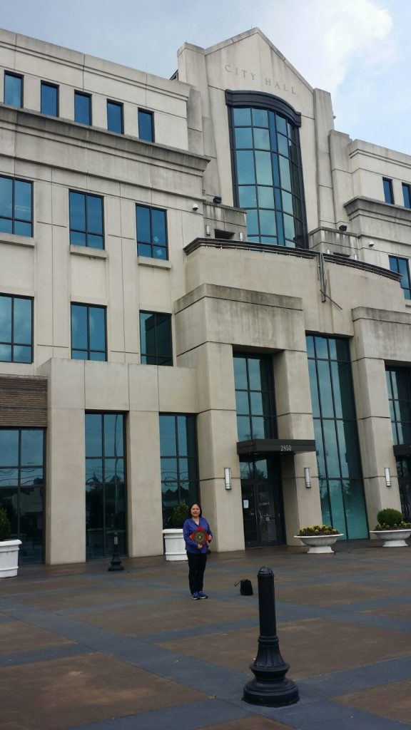 Master Ang with her Feng Shui loupan compass outside Birmingham, Alabama's city hall